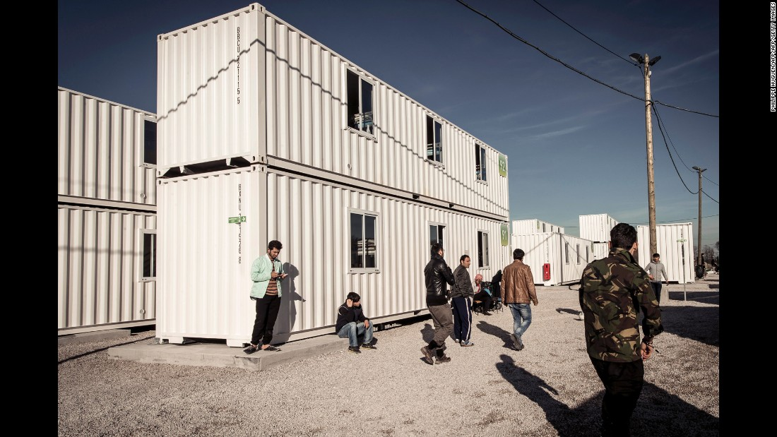 "Migrants walk past housing containers in ""The Jungle"" camp on February 16."