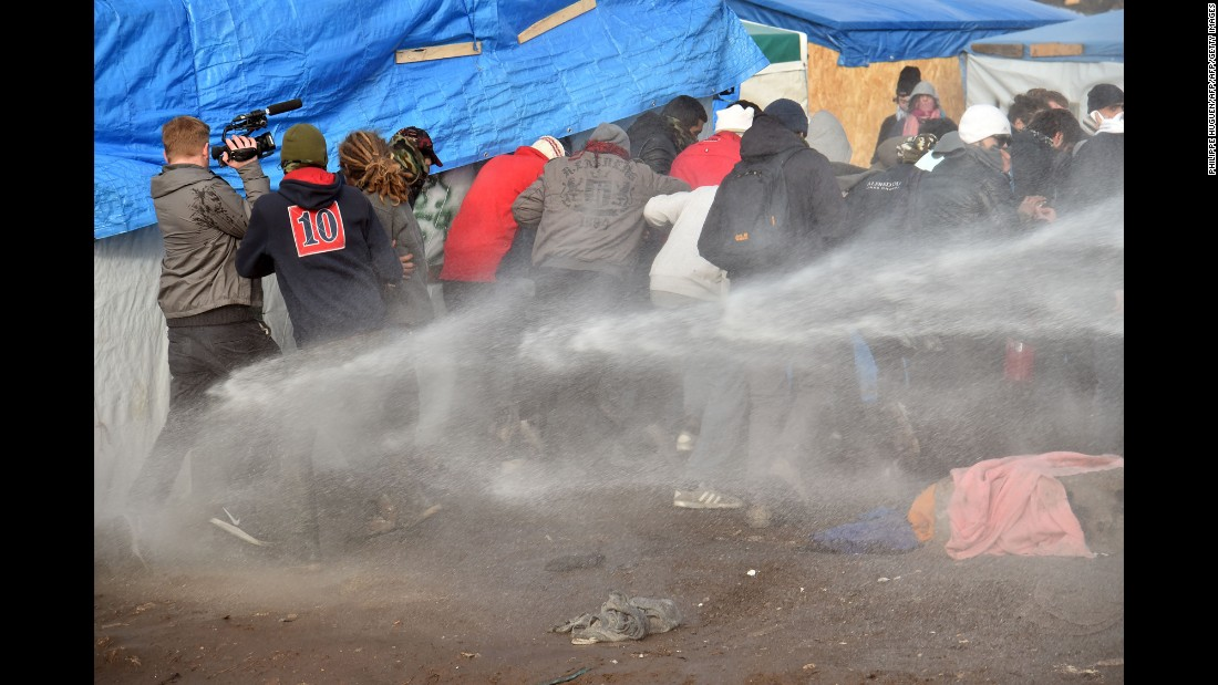 "Riot policemen spray water on migrants and refugees to disperse them during the dismantling of half of ""The Jungle"" on February 29. Two bulldozers and around 20 workers began destroying makeshift shacks, with 30 police cars and two anti-riot vans stationed nearby."