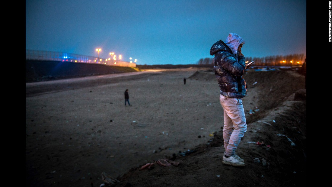 "A migrant makes a phone call near ""The Jungle"" on March 1. In the northern French port city of Calais, tensions were high as officials for a second day razed part of the camp, which has become a magnet for people hoping to reach Britain."