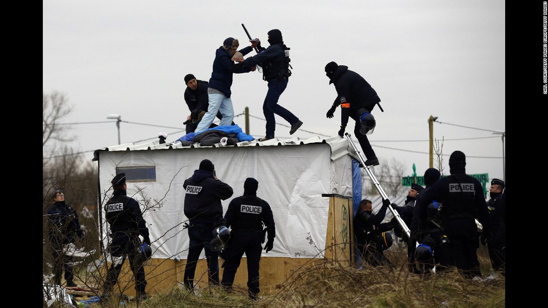 "A woman fights with a police officer as she is removed from the top of a hut as police clear ""The Jungle"" migrant camp on March 1. Police and demolition teams are continuing to dismantle makeshift shelters and relocating many people to purpose-built accommodation nearby."