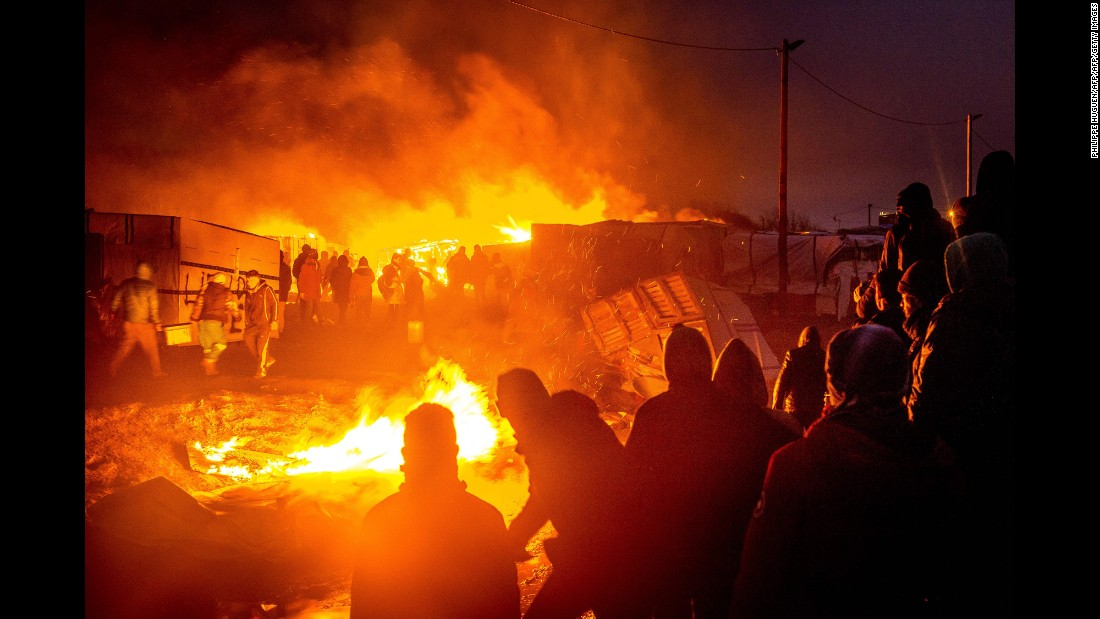 "Migrants stand next to a fire burning shacks in the southern part of ""The Jungle"" migrant camp March 1, as half of the camp is being dismantled."