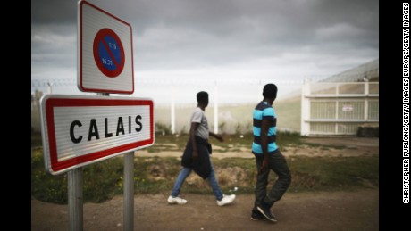 CALAIS, FRANCE - SEPTEMBER 06:  Migrants walk past secuirty fencing at the Jungle migrant camp on September 6, 2016 in Calais, France. The drop-in cafe for children is still facing closure and is embroiled in a legal battle with the french authorities. The cafe is run by volunteers and provides safe haven for up to 700 children living in the camp. Children attend language classes, are given free food and the opportunity to charge their mobile telephones so they can contact relatives in their homelands.  Last month a French court rejected a bid by Calais authorities to demolish the Jungle Cafe and other makeshift shops and restaurants but the decision may be facing an appeal.  (Photo by Christopher Furlong/Getty Images)