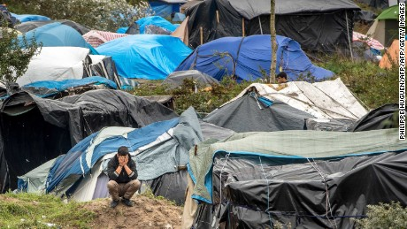 "A picture taken  in Calais on October 7, 2015 shows a site dubbed the ""New Jungle"", where some 3,000 people have set up camp -- most seeking desperately to get to England, . The slum-like migrant camp sprung up after the closure of notorious Red Cross camp Sangatte in 2002, which had become overcrowded and prone to violent riots. However migrants and refugees have kept coming and the ""New Jungle"" has swelled along with the numbers of those making  often deadly attempts to smuggle themselves across the Channel.  AFP PHOTO / PHILIPPE HUGUEN        (Photo credit should read PHILIPPE HUGUEN/AFP/Getty Images)"