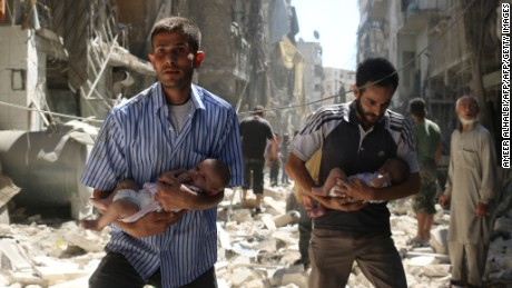 TOPSHOT - Syrian men carrying babies make their way through the rubble of destroyed buildings following a reported air strike on the rebel-held Salihin neighbourhood of the northern city of Aleppo, on September 11, 2016. Air strikes have killed dozens in rebel-held parts of Syria as the opposition considers whether to join a US-Russia truce deal due to take effect on September 12. / AFP / AMEER ALHALBI        (Photo credit should read AMEER ALHALBI/AFP/Getty Images)
