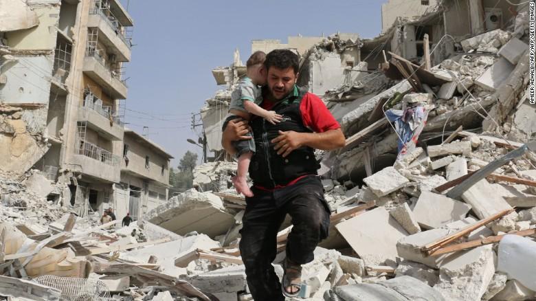 Um homem sírio carrega um bebê depois de removê-lo dos escombros de um edifício destruído.