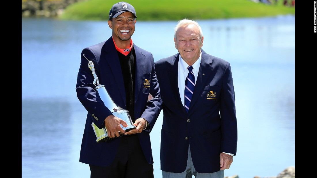 Tiger Woods is presented with a trophy by Palmer, after Woods won the final round of the 2013 Arnold Palmer Invitational Presented at Bay Hill Golf and Country Club.
