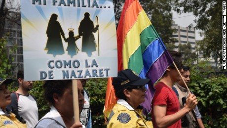 Members of the National Front for the Family march next to a gay community member (R) in Mexico City to protest President Enrique Pena Nieto's initiative to legalize gay marriage, on September 24, 2016.  The conservative National Front for the Family is strongly opposed to adoption by same-sex couples and to teaching about homosexuality and transsexuality in school sex education classes. / AFP / YURI CORTEZ        (Photo credit should read YURI CORTEZ/AFP/Getty Images)