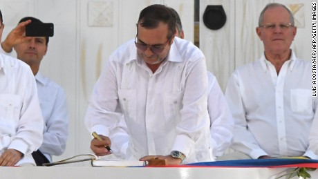 "The head of the FARC guerrilla Timoleon Jimenez, aka Timochenko, signs the historic peace agreement between the Colombian government and the Revolutionary Armed Forces of Colombia (FARC), in Cartagena, Colombia, on September 26, 2016  Colombia will turn the page on a half-century conflict that has stained its modern history with blood when the FARC rebels and the government sign a peace deal on Monday. President Juan Manuel Santos and the leader of the FARC, Rodrigo Londono -- better known by his nom de guerre, Timoleon ""Timochenko"" Jimenez -- are set to sign the accord at 2200 GMT in a ceremony in the colorful colonial city of Cartagena on the Caribbean coast. / AFP / Luis ACOSTA        (Photo credit should read LUIS ACOSTA/AFP/Getty Images)"