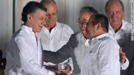 """Cuban President Raul Castro greets Colombian President Juan Manuel Santos (L) and the leader of the FARC, Rodrigo Londono -- better known by his nom de guerre, Timoleon """"Timochenko"""" Jimenez after the latter delivered a speech after signing the historic peace agreement between the Colombian government and the Revolutionary Armed Forces of Colombia (FARC), in Cartagena, Colombia, on September 26, 2016  The Colombian government and the leftist FARC rebel force signed a historic peace accord to end a half-century conflict that has killed hundreds of thousands of people. Santos and """"Timochenko"""" Jimenez, signed the deal at a ceremony in the Caribbean city of Cartagena, prompting loud cheers from the crowd which included numerous international dignitaries.  / AFP / Luis ACOSTA        (Photo credit should read LUIS ACOSTA/AFP/Getty Images)"""