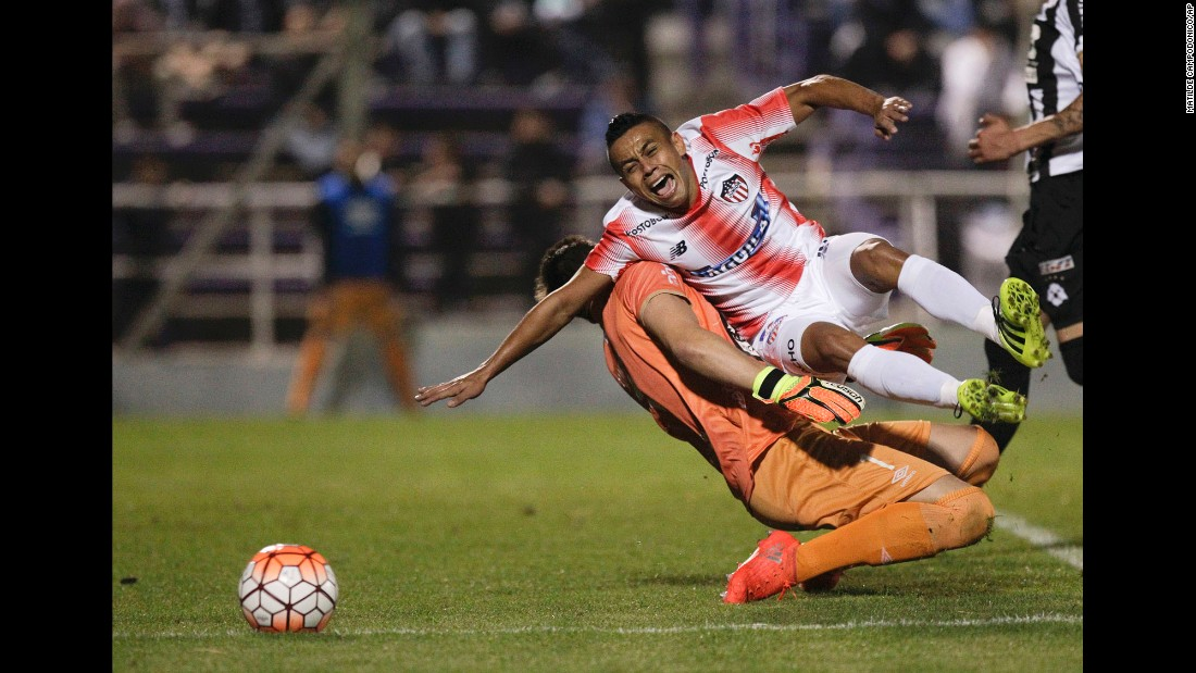 Vladimir Hernandez, a midfielder for the Colombian soccer club Junior, collides with Wanderers goalkeeper Leonardo Burian during a Copa Sudamericana match in Montevideo, Uruguay, on Wednesday, September 21. The match ended 0-0.