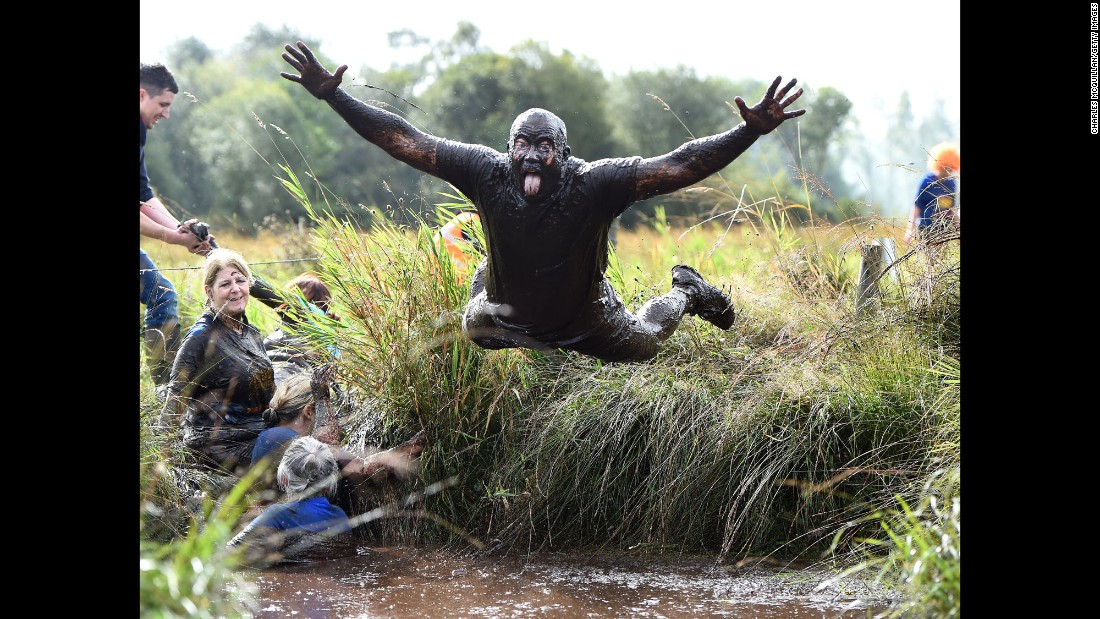 """A man dives into the mud Sunday, September 25, during a charity """"Mud Madness"""" race in Portadown, Northern Ireland."""