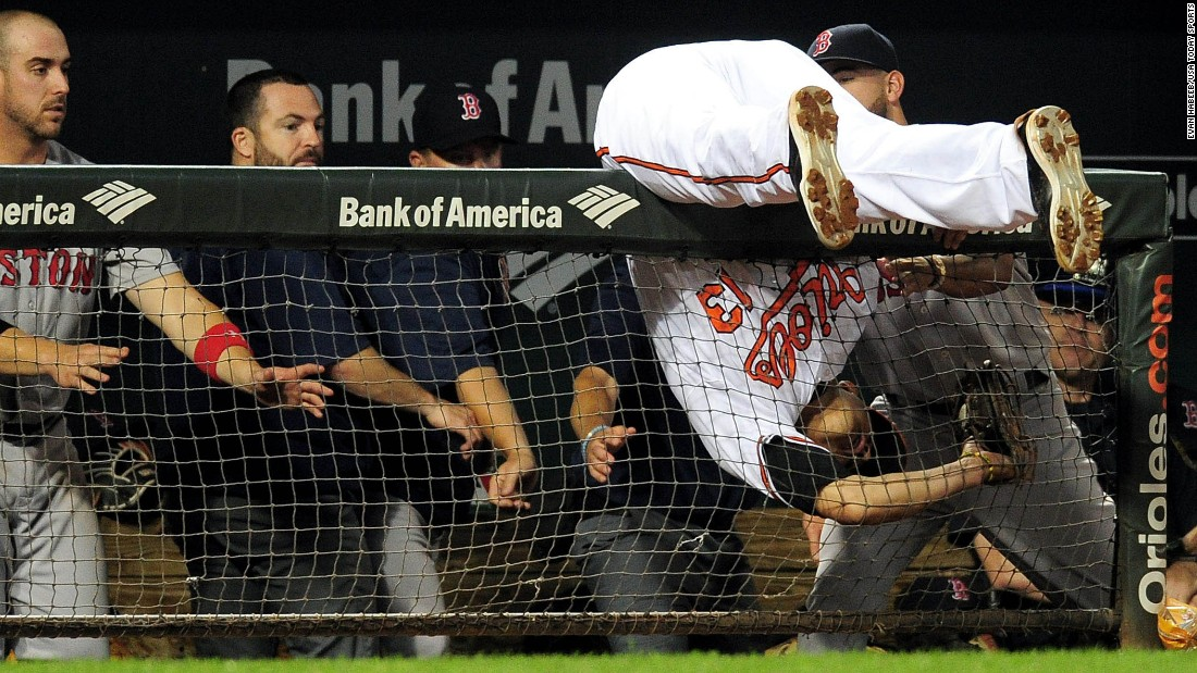 Baltimore third baseman Manny Machado falls over a dugout railing while catching a foul ball against Boston on Wednesday, September 21.