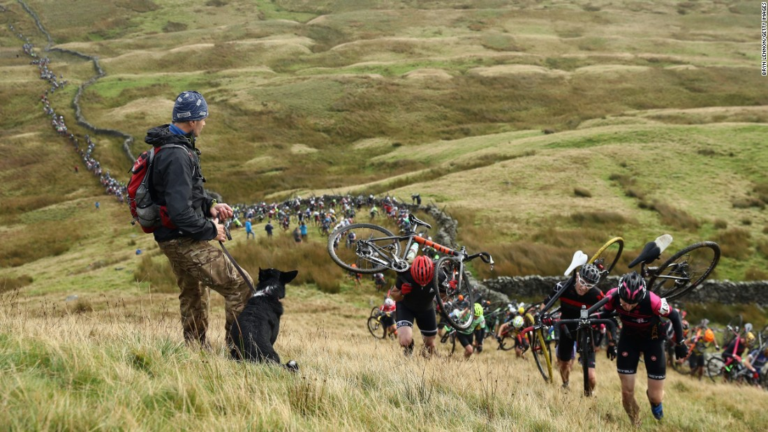 """A man and his dog watch riders climb Simon Fell at the start of the Three Peaks Cyclo-Cross race in Helwith Bridge, England, on Sunday, September 25. <a href=""""http://www.cnn.com/2016/09/19/sport/gallery/what-a-shot-sports-0920/index.html"""" target=""""_blank"""">See 28 amazing sports photos from last week</a>"""