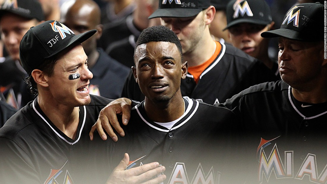 """Miami Marlins second baseman Dee Gordon is consoled by teammates after hitting a leadoff home run against the New York Mets on Monday, September 26. Gordon and the rest of the Marlins were mourning teammate Jose Fernandez, <a href=""""http://www.cnn.com/2016/09/25/us/mlb-pitcher-jose-fernandez-dead/"""" target=""""_blank"""">who died in a boating accident</a> Sunday at the age of 24. All the Marlins wore Fernandez jerseys during their game on Monday."""