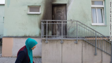 A woman wearing a headscarf walks past the entrance to the Fatih Camii Mosque in Dresden, eastern Germany, where traces of smoke can be seen after a bomb attack. Bomb attacks hit a mosque and a congress centre in the eastern German city of Dresden, police said, addding that they suspected a xenophobic and nationalist motive. No-one was injured in the twin explosives attacks late Monday, September 26, 2016 in the city that has become a hotspot for far-right protests amid Germany's huge migrant influx.  / AFP / dpa / Sebastian Kahnert / Germany OUT        (Photo credit should read SEBASTIAN KAHNERT/AFP/Getty Images)