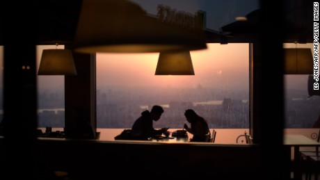 A couple eat in a restaurant overlooking the Seoul city skyline on February 13, 2015. Valentines day falls on February 14 when South Korean women usually give gifts to men, with the men reciprocating one month later on March 14. AFP PHOTO / Ed Jones        (Photo credit should read ED JONES/AFP/Getty Images)