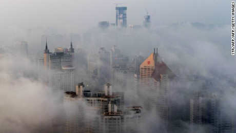 This photo taken on March 29, 2015 shows heavy fog covering buildings in Qingdao, east China's Shandong province. Falls in Chinese housing prices decelerated in March from the previous month, a survey showed on March 31, after authorities loosened mortgage and tax policies as growth in the world's second-largest economy slows.   CHINA OUT   AFP PHOTO        (Photo credit should read STR/AFP/Getty Images)