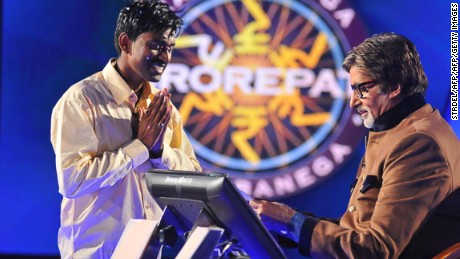 """Sushil Kumar, 27, (L) gestures as he receives his one million USD prize from Bachchan during the fifth season of the Indian version of """"Who Wants to be a Millionaire?"""""""