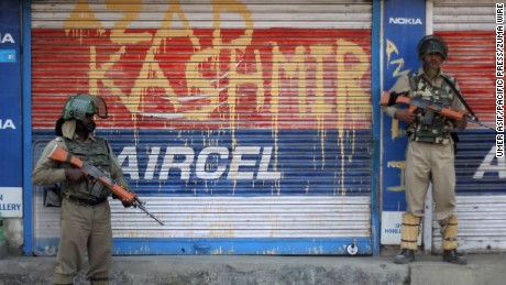 September 28, 2016 - Srinagar, Jammu and Kashmir, India - Indian paramilitary troopers stand guard near the graffiti 'Azad Kashmir' written on shop shutter in Srinagar in Indian controlled Kashmir. Tensions engulfed when a Hizb commander Burhan Wani was allegedly killed in an encounter with government forces. (Credit Image: © Umer Asif/Pacific Press via ZUMA Wire)