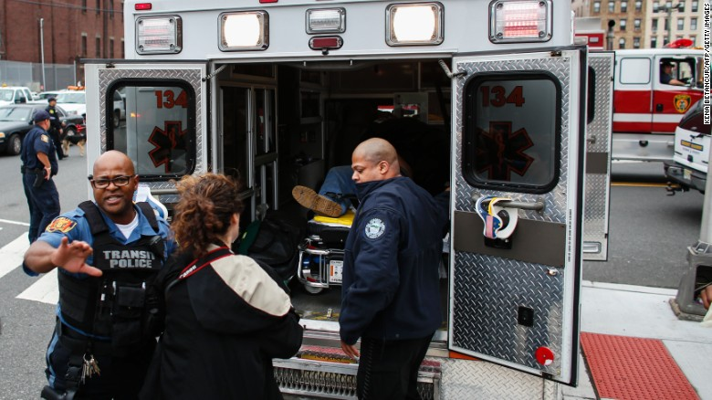 Emergency workers help an injured person into an ambulance outside the station.