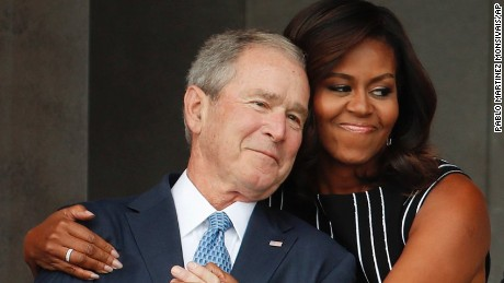 First lady Michelle Obama, center, hugs former President George W. Bush, as President Barack Obama and former first lady Laura Bush walk on stage at the dedication ceremony of the Smithsonian Museum of African American History and Culture on the National Mall in Washington, Saturday, Sept. 24, 2016. (AP Photo/Pablo Martinez Monsivais)
