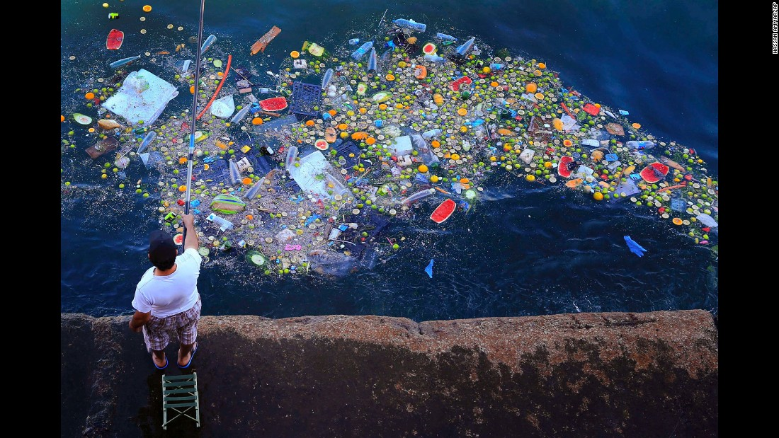 A man holds a fishing rod as floating trash hits the Mediterranean coastline in Beirut, Lebanon, on Thursday, September 29.