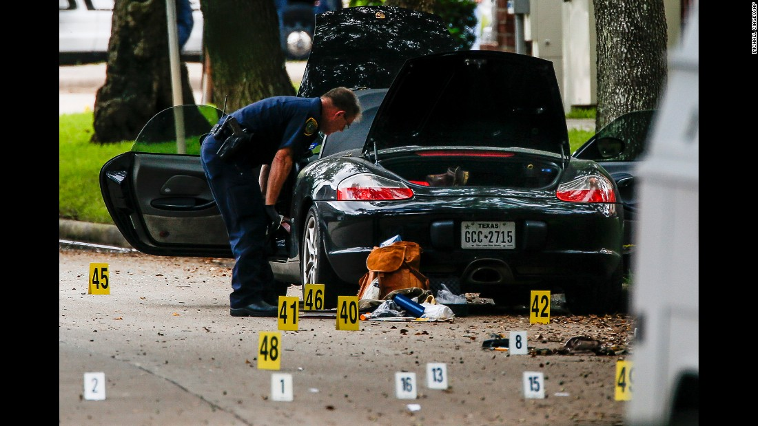 "A police officer investigates a car belonging to lawyer Nathan DeSai, <a href=""http://www.cnn.com/2016/09/26/us/houston-shooting/"" target=""_blank"">who shot and injured multiple people</a> before he was killed by police in Houston on Monday, September 26. DeSai was a lone gunman who was disgruntled over matters at the law firm where he worked, according to Houston's mayor, who said he'd been briefed on the shooting by police."
