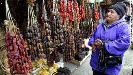 """An old woman looks for smoked seafood at """"Angelmo""""  typical market in Puerto Montt,1000 km south of Santiago, 26th October 2007. Products like mussels and clams are typical seafoofd from Chile's southern coast. AFP PHOTO MARTIN BERNETTI (Photo credit should read MARTIN BERNETTI/AFP/Getty Images)"""