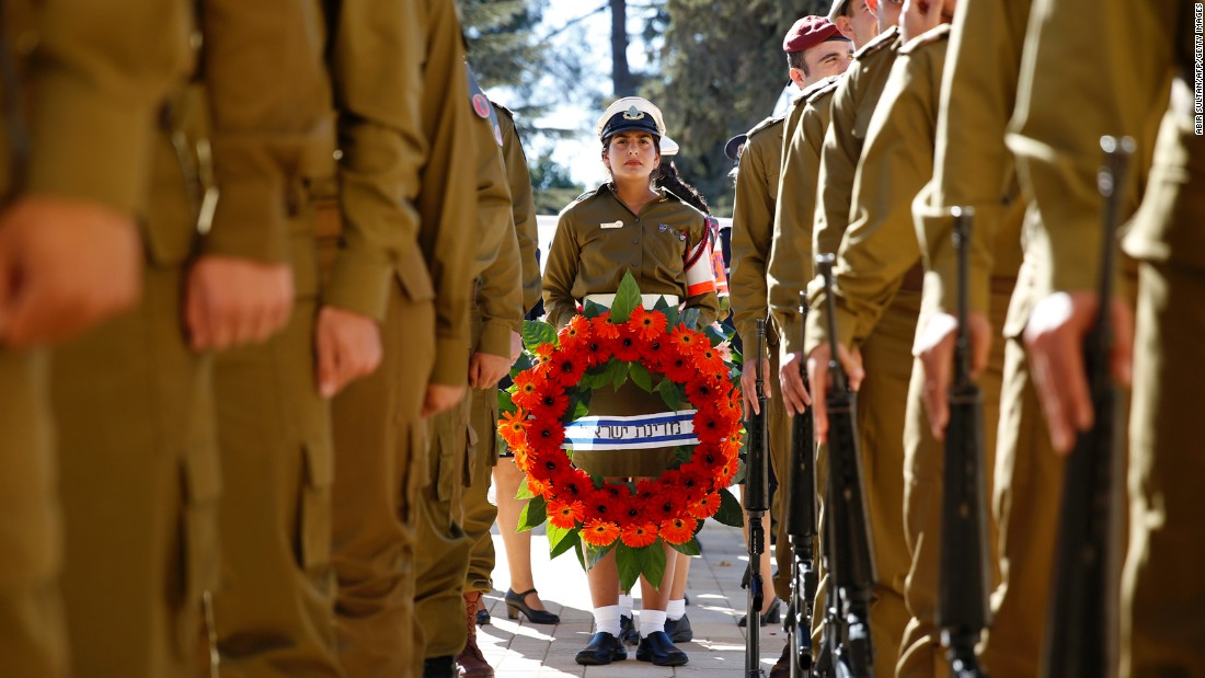 Israeli soldiers hold wreaths before making their way to the graveside.<br />
