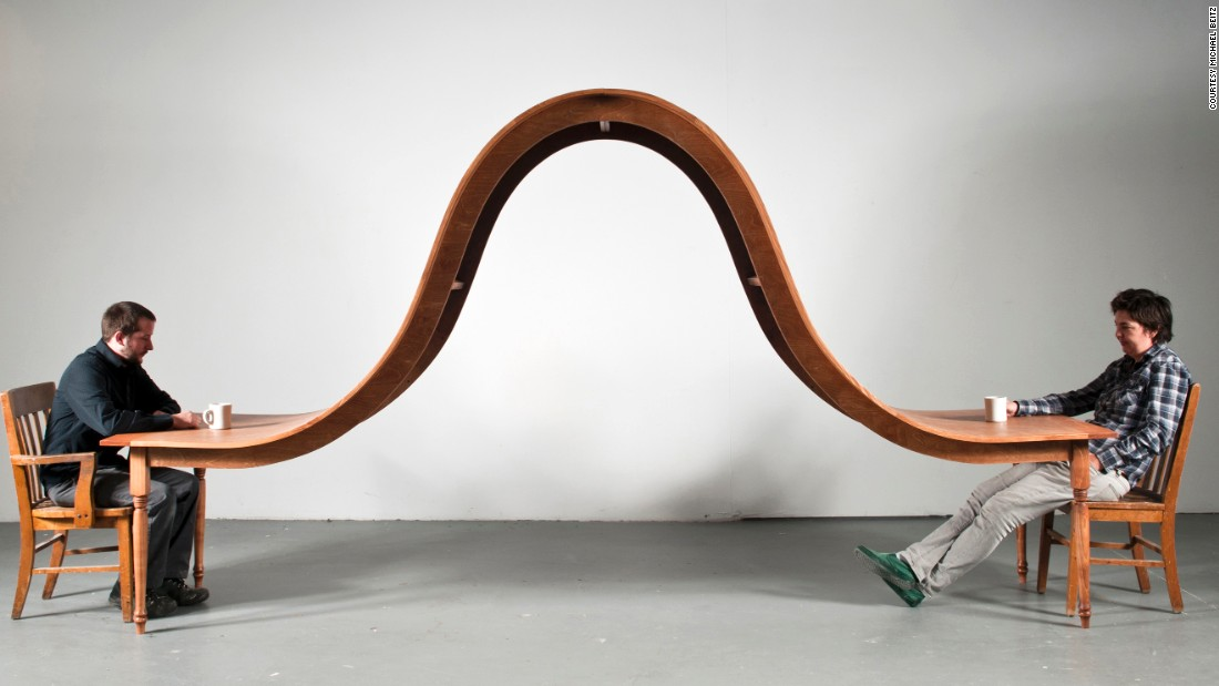 """Michael Beitz, who previously worked as a furniture-maker, gives common objects a literal twist to comment on different elements of the human condition. """"Dining Table,"""" for example, is meant to look at """"the silent tension that often exists between close people and the inability to communicate,"""" he says."""