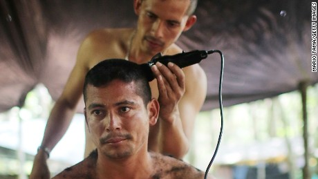 EL DIAMANTE, COLOMBIA - SEPTEMBER 26:  Revolutionary Armed Forces of Colombia (FARC) rebel Victor cuts the hair of a local supporter following the 10th Guerrilla Conference in the remote Yari plains where the peace accord was ratified by the FARC on September 26, 2016 in El Diamante, Colombia. The peace agreement attempts to end the 52-year-old guerrilla war between the FARC and the state, the longest-running armed conflict in the Americas which has left 220,000 dead. The final agreement is set to be signed later today and will then be put to vote by the public in a referendum on October 2. The plan calls for a disarmament and re-integration of most of the estimated 7,000 FARC fighters.  (Photo by Mario Tama/Getty Images)