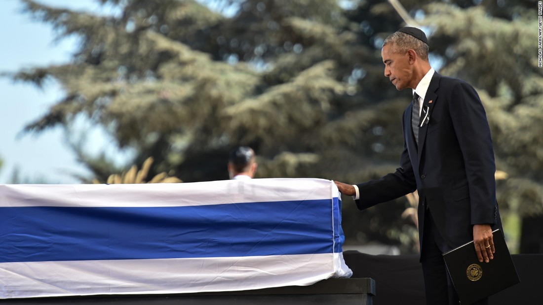 Obama touches Peres' coffin after speaking at the funeral.