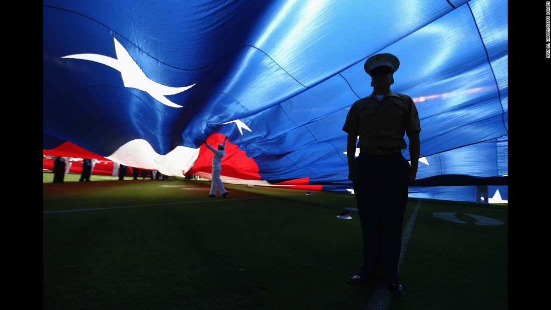 A U.S. Marine stands under a large American flag before an NFL football game in San Diego on Sunday, September 18.
