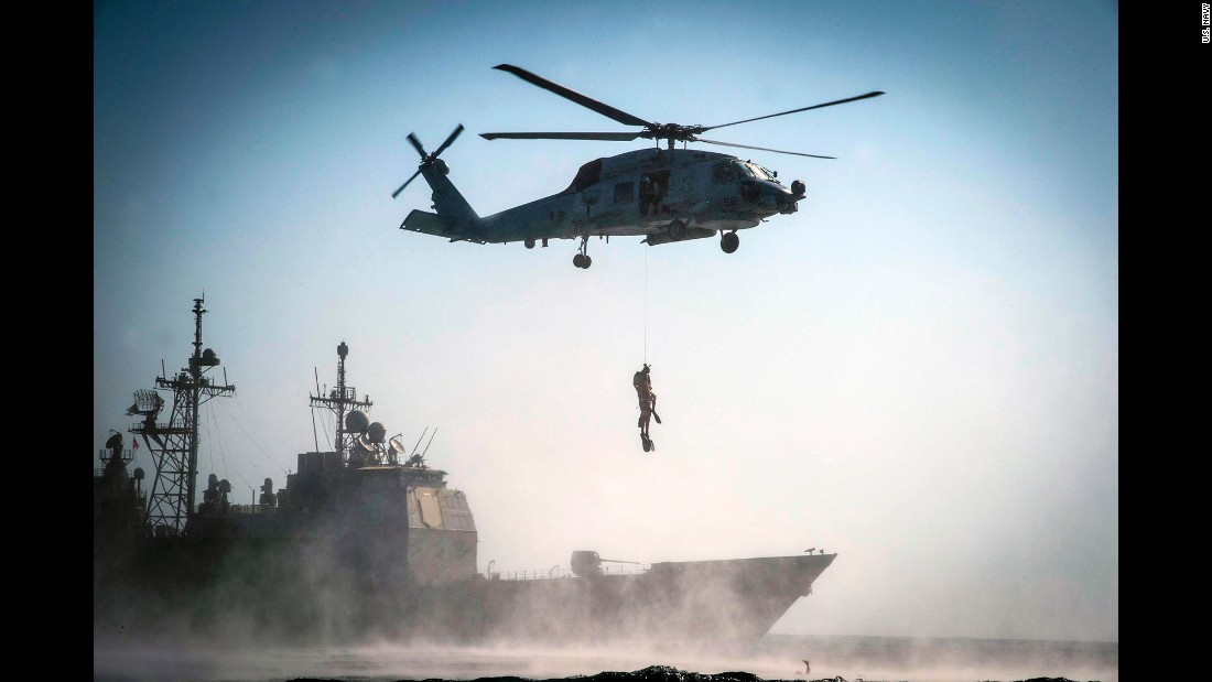 U.S. sailors are hoisted up by a helicopter during a search-and-rescue exercise in the Arabian Gulf on Friday, September 23.