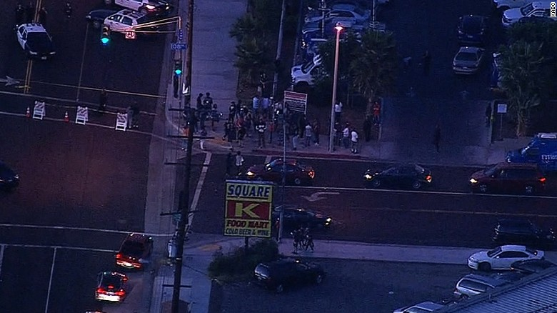 People gather near the scene of fatal shooting of a suspect by a Los Angeles police officer on Saturday.