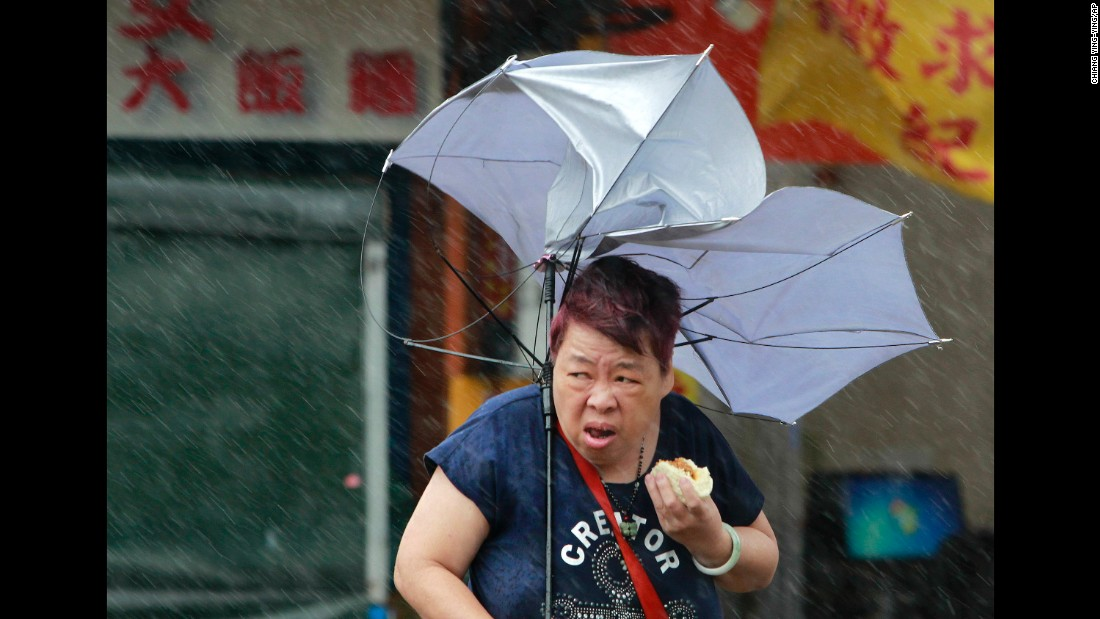 """A woman in Taipei, Taiwan, struggles with her umbrella as she eats food on Tuesday, September 27. Typhoon Megi brought powerful winds to the island before <a href=""""http://www.cnn.com/2016/09/26/asia/typhoon-megi-taiwan-weather/index.html"""" target=""""_blank"""">making landfall in mainland China.</a>"""