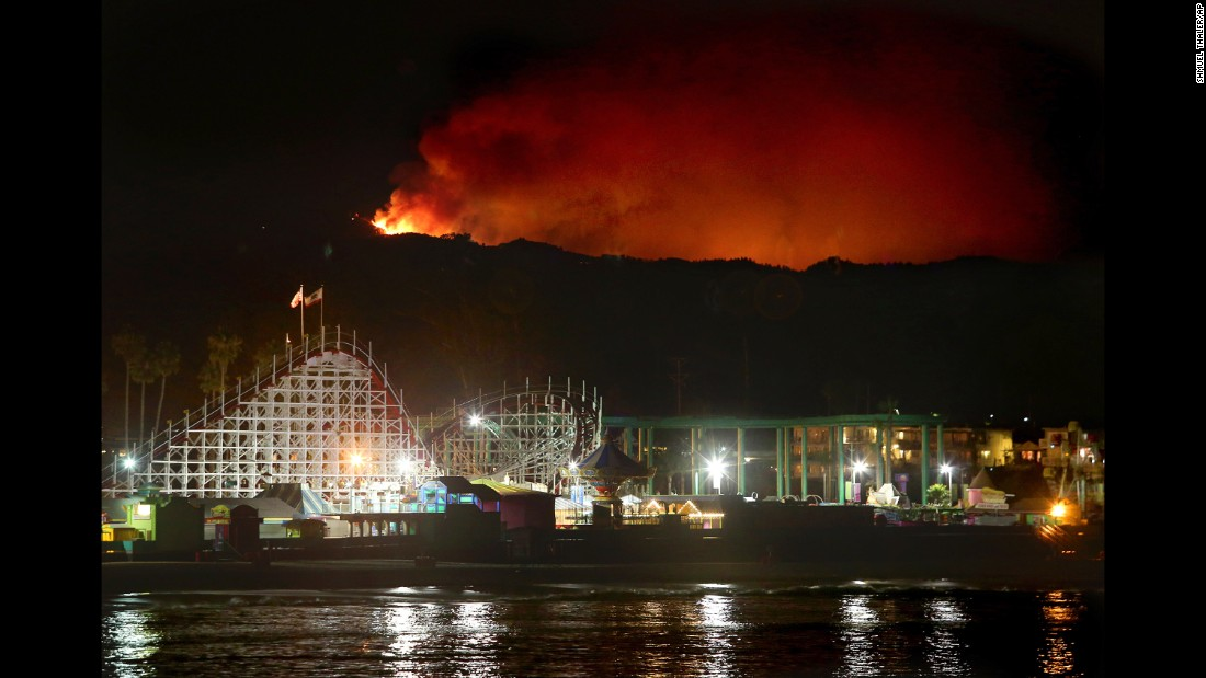 The Loma Fire rages in the Santa Cruz Mountains behind the Giant Dipper roller coaster Monday, September 26, in Santa Cruz, California.