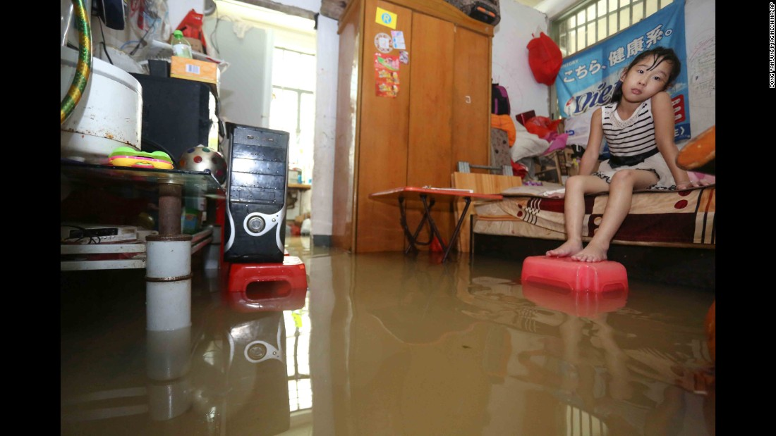 """A girl sits on her bed after heavy rain caused by <a href=""""http://www.cnn.com/2016/09/12/asia/typhoon-meranti-weather/"""" target=""""_blank"""">Typhoon Meranti</a> flooded her home in Jinjiang, China, on Thursday, September 15."""