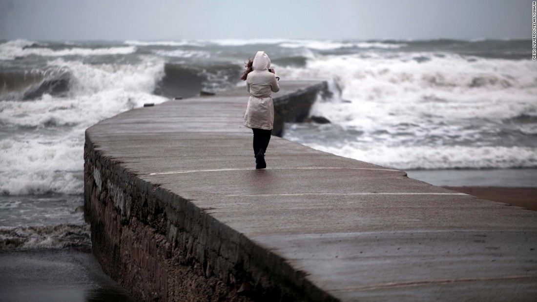 A woman takes pictures of strong waves in Mar del Plata, Argentina, on Tuesday, September 6.