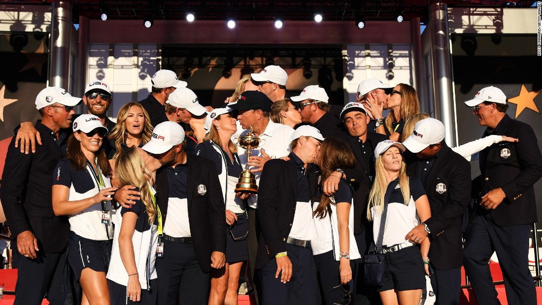 """Golfer Rickie Fowler shrugs as his U.S. teammates kiss their wives and girlfriends <a href=""""http://www.cnn.com/2016/10/03/golf/ryder-cup-2016-reactions-obama-arnold-palmer/index.html"""" target=""""_blank"""">during a team photo</a> on Sunday, October 2. The team had just won the Ryder Cup."""