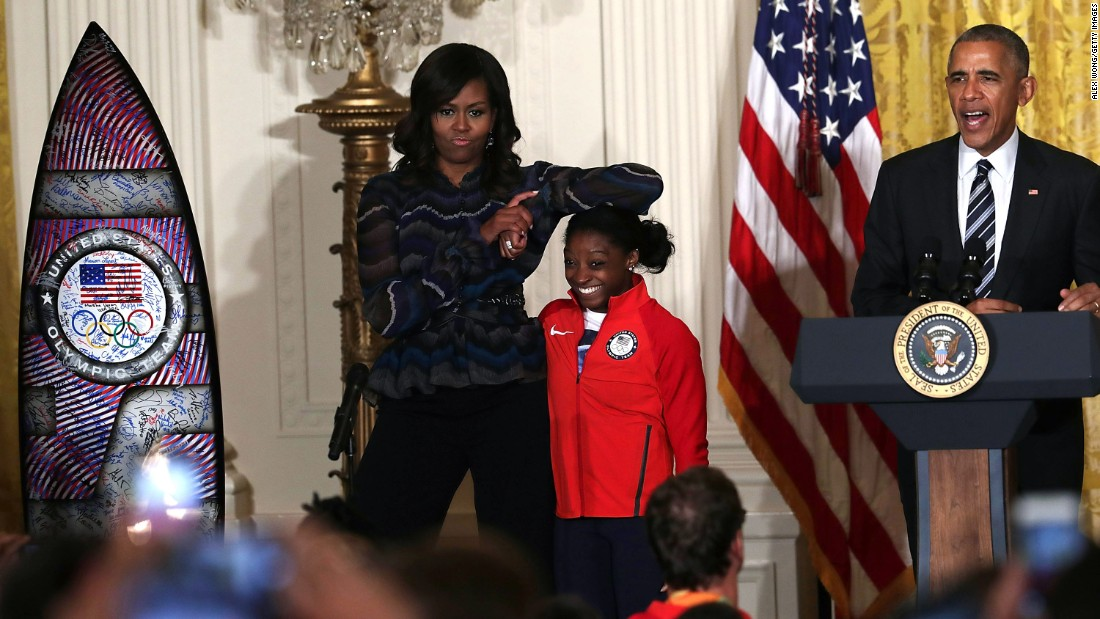 First lady Michelle Obama rests her elbow on the head of U.S. gymnast Simone Biles, Olympic champion, during a White House event on Thursday, September 29. The Obamas were welcoming the U.S. Olympic and Paralympic teams to the White House.
