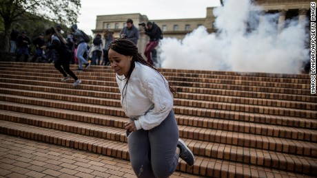 A student runs from an exploding stun grenade thrown by anti-riot police as they disperse a demonstration by students over fee increases at the Witwatersrand University in Johannesburg on October 4, 2016.