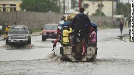 """A tap tap (public transportation) crosses the water left by the rain after hurricane Matthew, in Port-au-Prince, on October 4, 2016.  Hurricane Matthew made landfall in southwestern Haiti early Tuesday, crashing ashore as a powerful Category Four storm, US weather forecasters said. The National Hurricane Center said Matthew made landfall as an """"extremely dangerous"""" storm near the village of Les Anglais at around 7 am (1100 GMT) with maximum sustained winds of around 145 miles (230 kilometers) per hour.  / AFP / HECTOR RETAMAL        (Photo credit should read HECTOR RETAMAL/AFP/Getty Images)"""