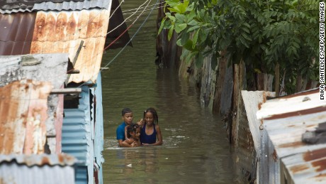 Picture taken in the flooded neighborhood of La Puya, in Santo Domingo on October 4, 2016 after the passage of Hurricane Matthew through Hispaniola -- the island that the Dominican Republic shares with Haiti.