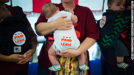 Tanya Snyder holding Milo Evans-Snyder, 5 months old, left, Jessica Champagne holding Benjamin Roth-Champagne, 3 moths old, center, and Jamie Davis Smith holding Adam Smith, 10 months old, right, stand in the hallway after dozens of parents with toddlers and people sat through a DC Council hearing to show support for a paid family leave bill at the John A. Wilson Building in Washington, DC in 2015.