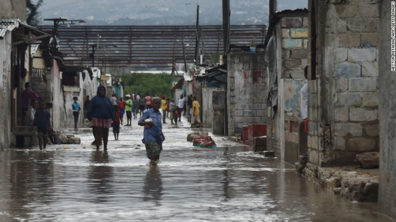 People walk down flooded streets in the Haitian capital of Port-au-Prince on Tuesday.