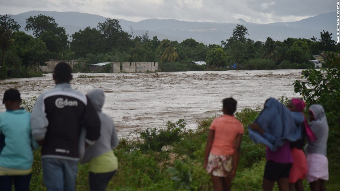 People observe the flooding of a river near Port-au-Prince on October 4.