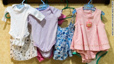 Baby clothes hang on the wall of the nursery area at Sunrise Senior Living.