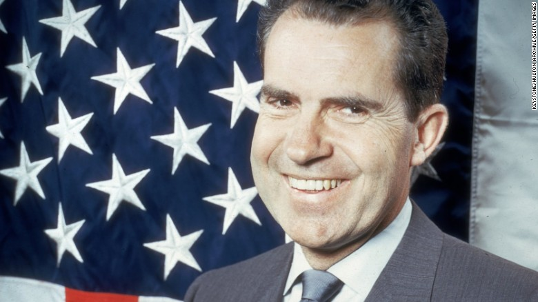 1960:  Republican presidential candidate Vice-President Richard Nixon (1913 -1994) laughing as he poses in front of the stars and stripes.  (Photo by Keystone/Getty Images)