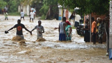 People try to cross the overflowing La Rouyonne river in the commune of Leogane, south of Port-au-Prince, October 5, 2016.Haiti and the eastern tip of Cuba -- blasted by Matthew on October 4, 2016 -- began the messy and probably grim task of assessing the storm's toll. Matthew hit them as a Category Four hurricane but has since been downgraded to three, on a scale of five, by the US National Hurricane Center. / AFP / HECTOR RETAMAL        (Photo credit should read HECTOR RETAMAL/AFP/Getty Images)